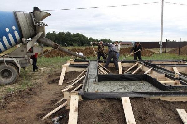 Процесс заливки бетона из машины в опалубку для фундамента