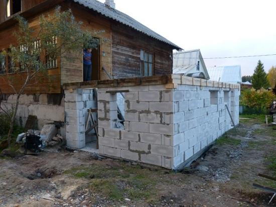 Процесс строительства пристройки к деревянному дому из пеноблоков