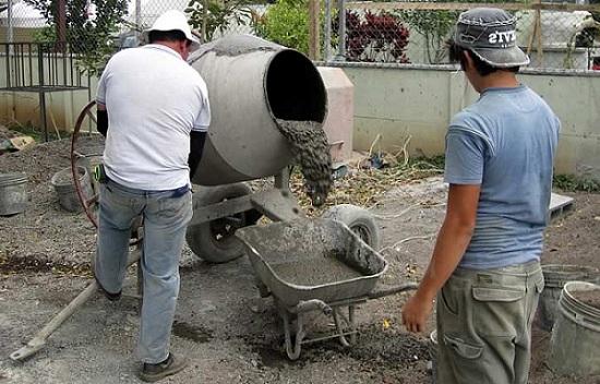Процесс выгрузки готового бетона из бетономешалки