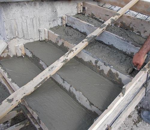 Процесс заливки бетона в опалубку для лестницы