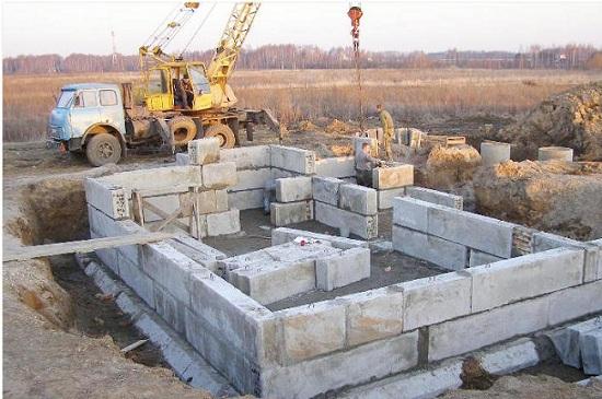 Процесс укладки блоков с помощью подъемного крана